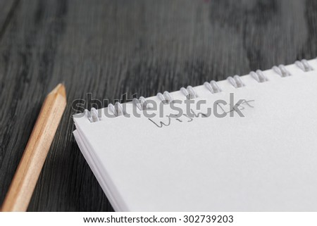 closeup photo of open empty notepad with wish list phrase, on wood table - stock photo