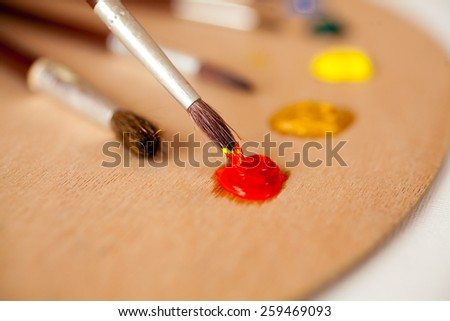 Closeup photo of professional paintbrush dipped in red oil paint on palette - stock photo