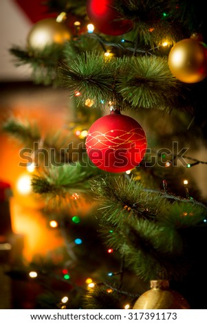 Closeup photo of red Christmas ball on fir tree next to fireplace - stock photo