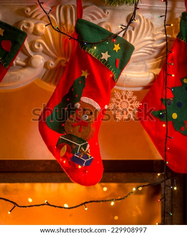 Closeup photo of red christmas stockings hanging on fireplace - stock photo