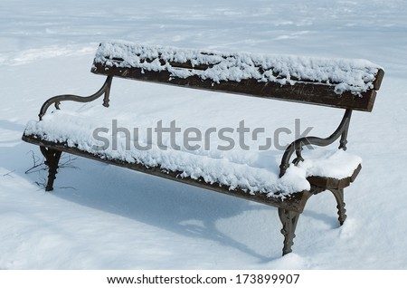 Closeup photo of snowy bench in the park in winter - stock photo