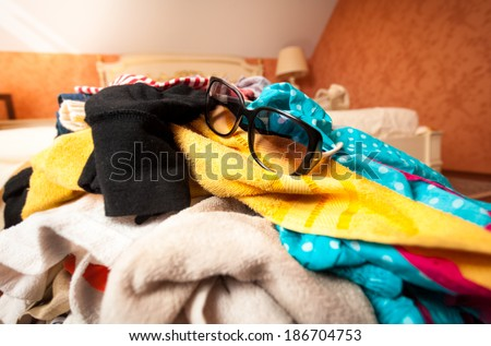 Closeup photo of sunglasses on pile of clothes in suitcase - stock photo