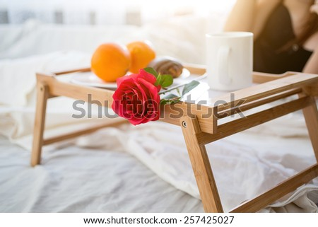 Closeup photo of tray with breakfast and red rose on bed at hotel room - stock photo