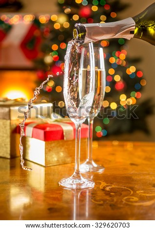 Closeup photo of two champagne glasses on Christmas dining table - stock photo