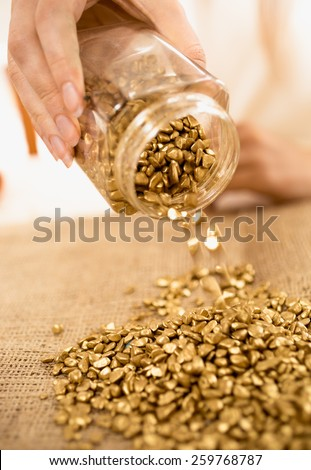 Closeup photo of woman holding bullion full of gold nuggets - stock photo