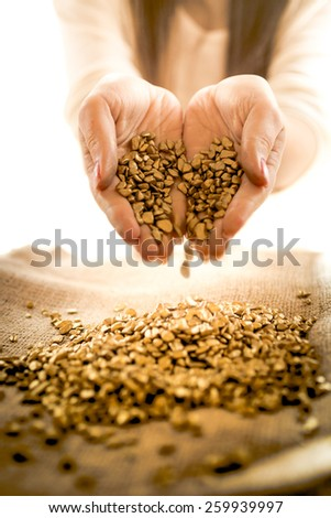 Closeup photo of woman holding golden heap in hands - stock photo