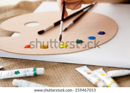 Closeup photo of woman holding paintbrush and choosing color on the pallet - stock photo