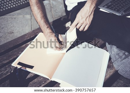 Closeup photo student writing textbook message. Studying at the University, working project,  preparation for exams. Blank book, notebook bench. Horizontal, film effect - stock photo