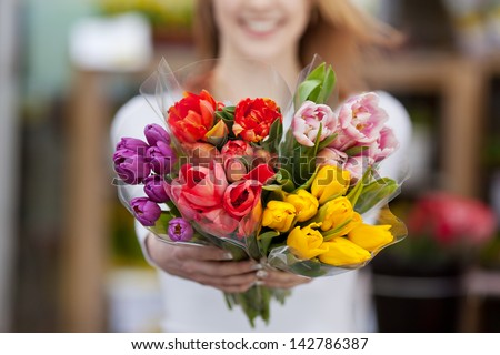Closeup photograph of a woman showing a bunch of assorted flowers. - stock photo