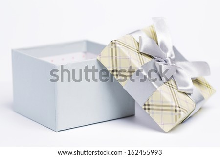 Closeup picture of a beautiful open present package over a white background  - stock photo