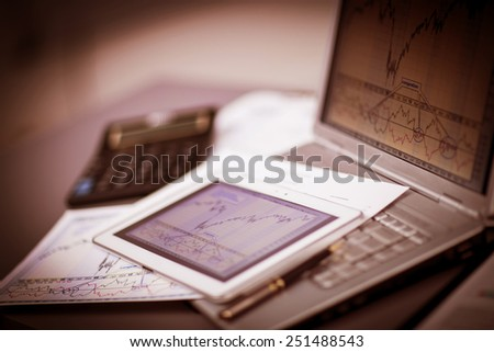 Closeup picture of a keyboard with a phone and tablet lying above it - stock photo