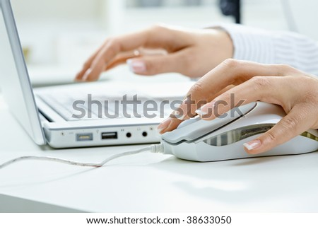 Closeup picture of computer keyboard and female hand using mouse. - stock photo