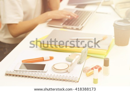 Closeup picture of cosmetics represented among exercise-books, documents and university, colleage or school things for studying. Toned image.  - stock photo