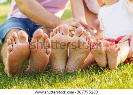 Closeup picture of family feets lying in line at green grass - stock photo