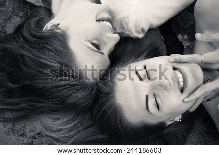 closeup picture of happy girl friends relaxing head to head happy smiling - stock photo