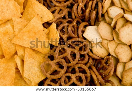 Closeup picture of tortilla chips, pretzels and spicy crackers - stock photo
