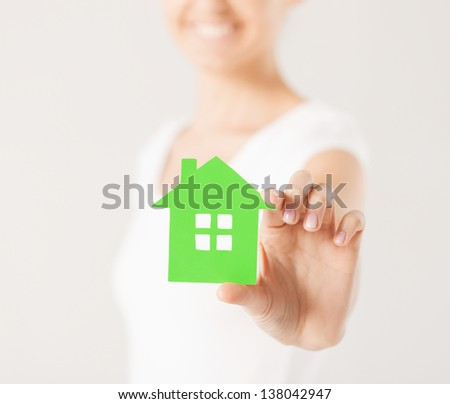 closeup picture of woman hands holding green house - stock photo