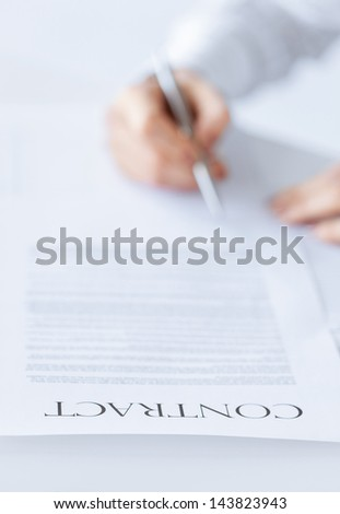 closeup picture of woman hands signing contract - stock photo