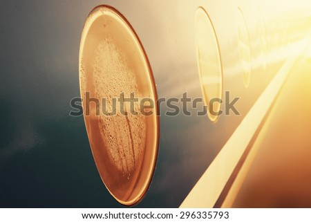 closeup porthole of flying airplane on sunset. vintage picture - stock photo