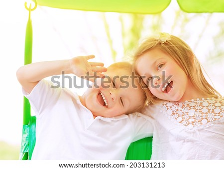 Closeup portrait adorable children having fun on swing outdoors, best friends playing on backyard in daycare, healthy and happy lifestyle, strong friendship concept - stock photo