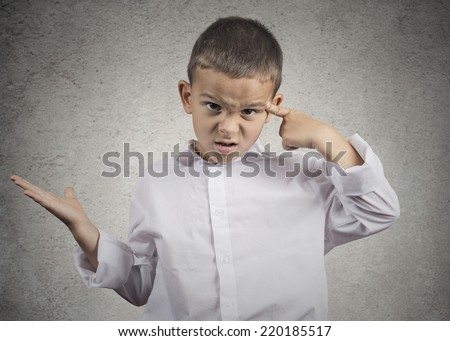 Closeup portrait angry mad child boy gesturing with his finger against temple asking are you crazy? Isolated grey wall background. Negative human emotions facial expression feeling body language - stock photo