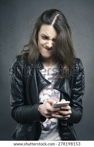 Closeup portrait angry young girl looking at phone seeing bad news or photos with disgusting emotion on her face texture background. Human emotion, reaction, expression  - stock photo