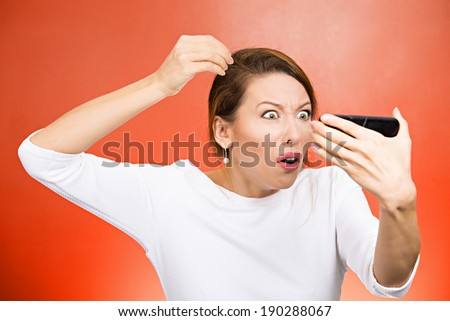 Closeup portrait, annoyed woman looking worried at white color hair or balding, isolated red orange background. Negative human emotion facial expression feelings, attitudes, reaction, situation - stock photo