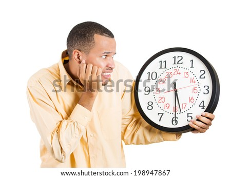 Closeup portrait anxious business man, student, leader holding wall clock, stressed, pressured by lack, running out of time, late meeting, isolated white background. Human emotions, facial expressions - stock photo