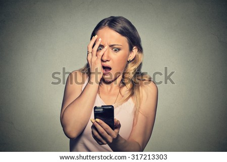 Closeup portrait anxious scared young girl looking at phone seeing bad news photos message with disgusting emotion on her face isolated on gray wall background. Human reaction, expression - stock photo