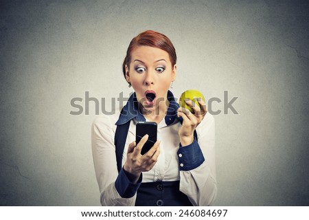Closeup portrait anxious shocked young business woman looking at phone seeing bad news or photos with disgusting emotion on her face isolated grey wall background. Human emotion, reaction, expression - stock photo
