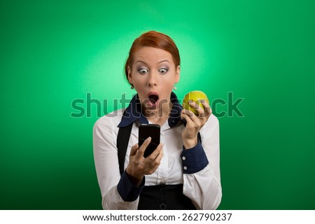 Closeup portrait anxious shocked young business woman looking at phone seeing bad news or photos with disgusting emotion on her face isolated green background. Human emotion, reaction, expression - stock photo