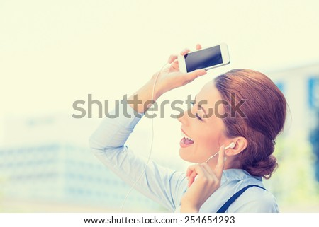 Closeup portrait attractive smiling business woman walking on street listening music on mobile smart phone outdoor laughing isolated city background. Positive human emotion face expression. Urban life - stock photo