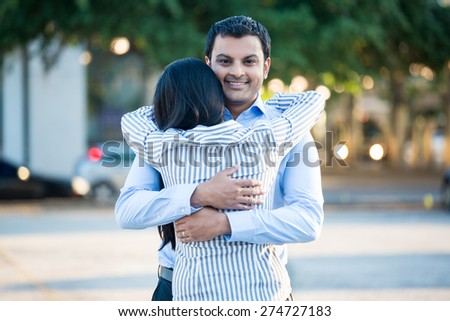 Closeup portrait back view, young couple in blue shirt, hugging, smiling, isolated outdoors outside background. Happy moments, positive emotions - stock photo