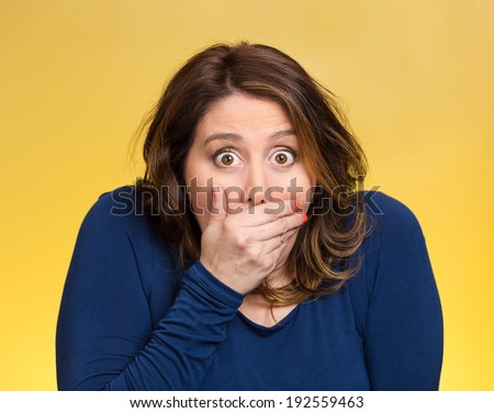 Closeup portrait beautiful, middle aged shocked young woman, covering her mouth, wide open eyes, isolated yellow background. Negative human emotion, facial expression, feeling, signs, symbol, reaction - stock photo