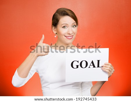 Closeup portrait beautiful smiling, happy business woman holding sign goal, giving thumbs up isolated red background. Positive emotions, facial expressions, reaction, attitude, determination, dynamism - stock photo