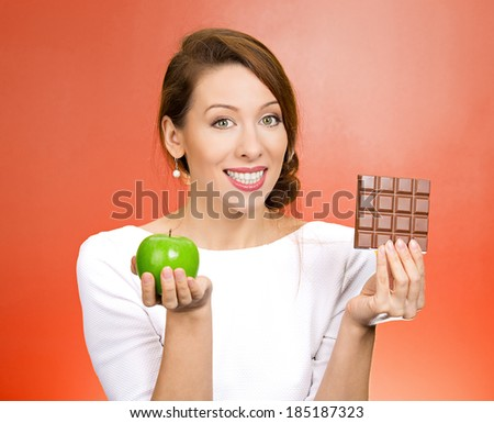 Closeup portrait, beautiful, smiling young woman offering nutritious lime apple as an alternative to unhealthy square milk chocolate, isolated red background. Food diet option situations, dilemma. - stock photo