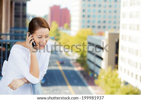 Closeup portrait beautiful woman talking on cell, mobile phone relaxed on balcony of her apartment isolated city background. Urban life style. Positive face expression, emotions. Travel, hotel concept - stock photo