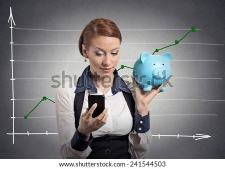 Closeup portrait business woman corporate employee holding piggy bank looking at smart phone isolated on grey wall office background financial chart growing up. Savings investment banking concept  - stock photo