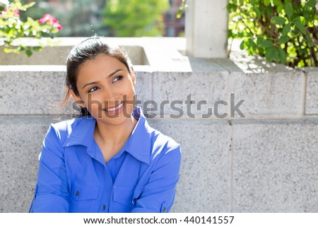 Closeup portrait, charming upbeat smiling joyful happy young woman looking upwards daydreaming something nice, isolated outdoors gray background. Positive human facial expressions feelings - stock photo