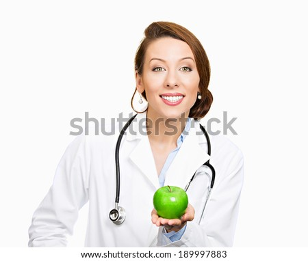 Closeup portrait, confident happy health care professional, doctor, nurse in lab coat, offering you fruit, isolated white background. Apple a day keeps doctor away concept. Nutrition, healthy diet - stock photo