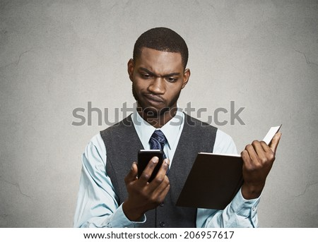 Closeup portrait confused, skeptical business man, executive reading news on smart phone, holding book isolated black background. Human face expression, emotion, body language, corporate lifestyle - stock photo