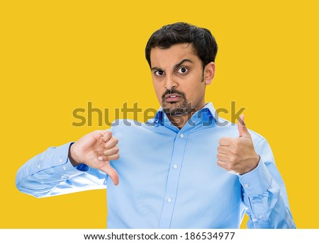 Closeup portrait, confused, young man pointing in two different directions, not sure if good or bad, showing thumbs up, down simultaneously, isolated yellow background. Emotion, face expression - stock photo