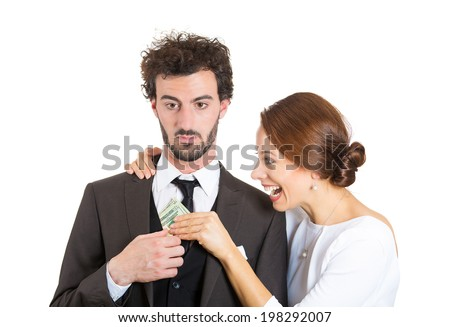 Closeup portrait couple, excited woman, girlfriend pulling money out of man pocket, he looks skeptical, surprised, annoyed isolated white background. Shopping lover, reckless spending. Face expression - stock photo