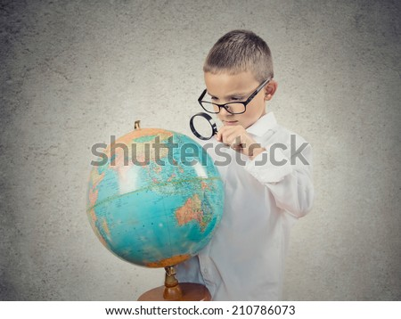 Closeup portrait curious child holding earth globe map in his hand, looking through magnifying loupe, picking his next destination isolated grey wall background. Human facial expression.Travel concept - stock photo