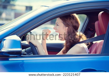 Closeup portrait displeased angry pissed off aggressive woman driving car shouting at someone hand fist up in air isolated traffic background. Emotional intelligence concept. Negative human expression - stock photo