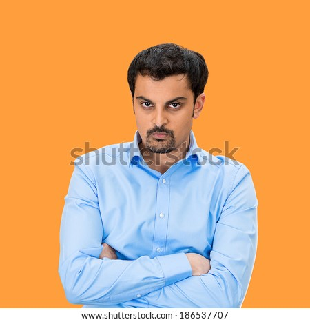 Closeup portrait, displeased, pissed off, angry, grumpy business man, bad attitude, arms crossed, folded, looking at you, isolated orange background. Negative human emotion, facial expression, feeling - stock photo
