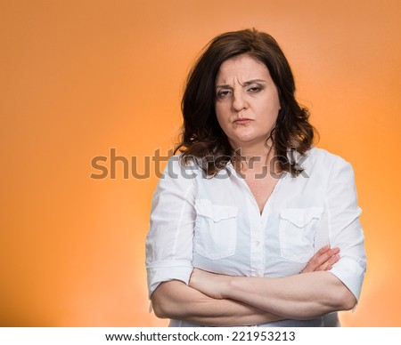 Closeup portrait displeased pissed off angry grumpy pessimistic woman with bad attitude, arms crossed looking at you, isolated orange background. Negative human emotion facial expression feeling - stock photo