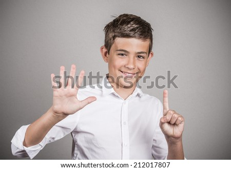 Closeup portrait excited happy young man showing 6 fingers, giving number six sign, isolated grey wall background. Positive human emotion, face expression, attitude, reaction, perception body language - stock photo