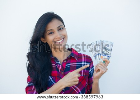 Closeup portrait, excited successful young business woman in plaid shirt holding money dollar bills in hand isolated white wall background. Positive emotion facial expression feeling. Financial reward - stock photo