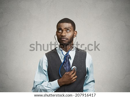 Closeup portrait executive man, business person, worker listening to his heart with stethoscope looking up isolated grey background. Preventive medicine, financial condition concept. Face expressions - stock photo